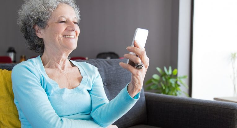 Happy laughing senior woman talking to grandchildren. Mature grey haired lady sitting on couch in living room and using phone for video call. Video call concept