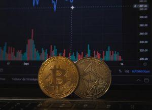 Duas moedas douradas em destaque e, ao fundo, um gráfico financeiro
