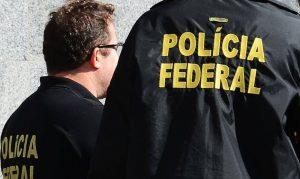 Dois agentes da Polícia Federal de costas. Imagem foca no nome 'Polícia Federal' que está atrás da farda de um deles