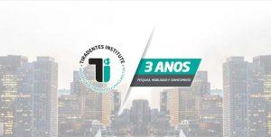 Imagem de divulgação do Colóquio Internacional, com prédios ao fundo, logo do Tiradentes Institute, e marca de aniversário de 3 anos da instituição