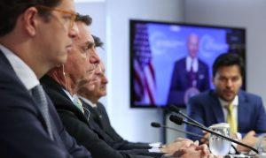 Os presidentes Jair Bolsonaro (de fone) e Joe Biden (na tela ao fundo) participam da Cúpula do Clima: agenda ambiental em discussão