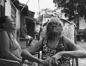 Foto em preto em branco com duas senhoras sentadas à frente de casa no quilombo da Maloca